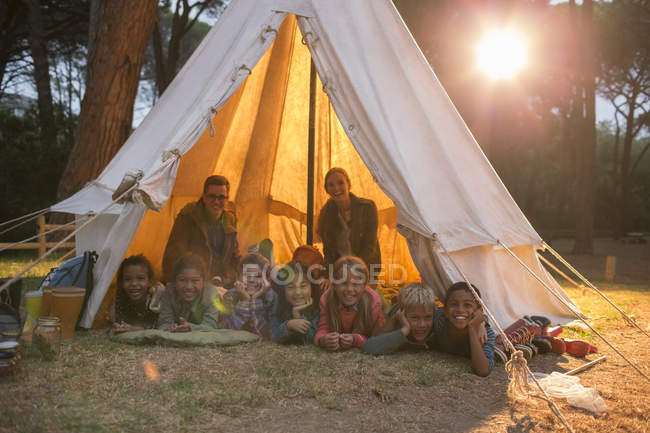 Students and teachers smiling in teepee at campsite — Stock Photo