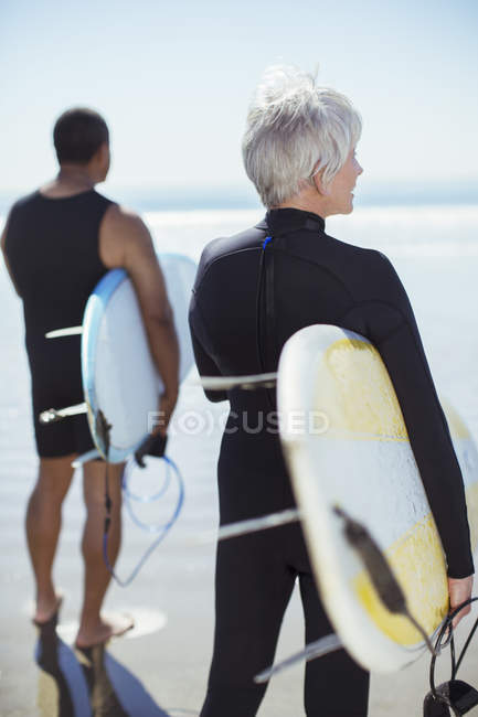Rückansicht eines älteren Paares mit Surfbrettern am Strand — Stockfoto