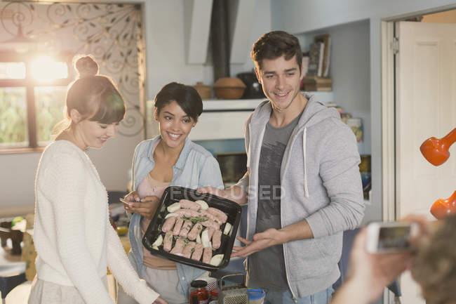 Coinquilini giovani amici cucinare in posa per amico utilizzando la fotocamera del telefono — Foto stock