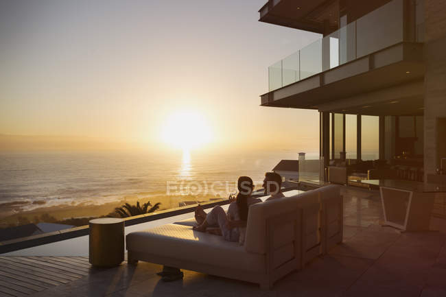 Tranquil sunset ocean view beyond silhouette of couple on luxury home showcase chaise lounge — Stock Photo