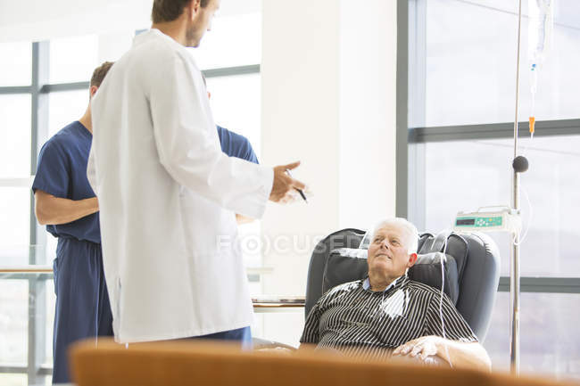 Deux médecins parlent à un patient âgé sous traitement médical en clinique externe — Photo de stock