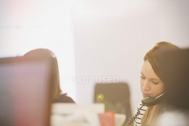 Businesswoman talking on telephone in modern office — Stock Photo
