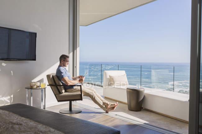 Uomo utilizzando tablet digitale con vista sull'oceano soleggiato — Foto stock