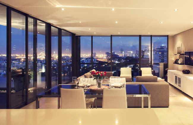 Illuminated modern living room overlooking city — Stock Photo