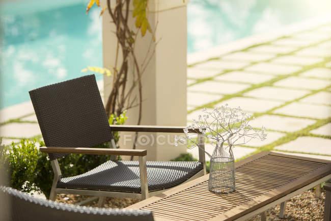 Blumenschmuck am Tisch am sonnigen Pool — Stockfoto