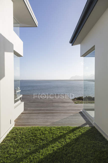 Modern home showcase exterior courtyard with sunny, tranquil ocean view — Stock Photo