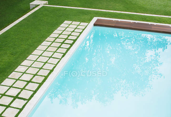 Paving stones in a row along swimming pool in backyard — Stock Photo
