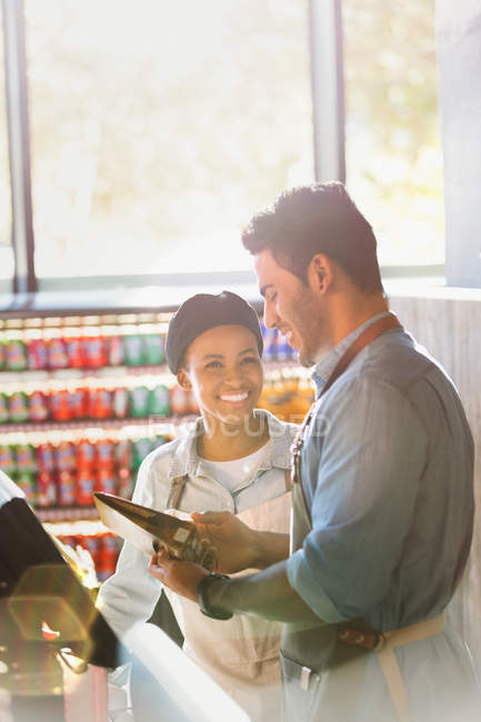 Workers smiling and talking at grocery store market checkout — Stock Photo
