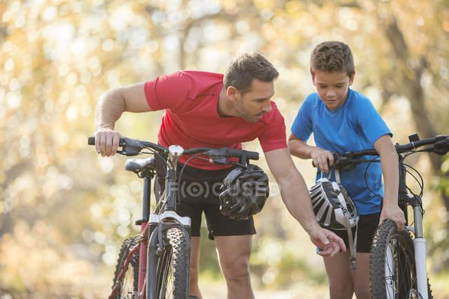 Father and son examining wheel on mountain bike — Stock Photo