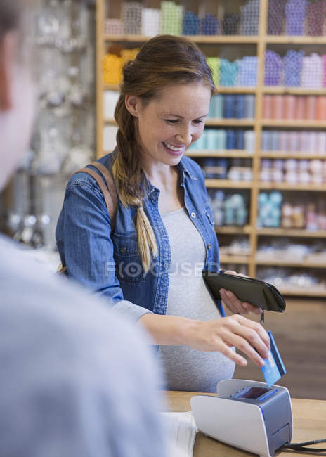 Pregnant woman using credit card reader in shop — Stock Photo