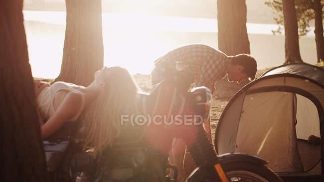 Молодой человек готовит палатку на стоянке рядом с женщиной, лежащей на мотоцикле — стоковое фото