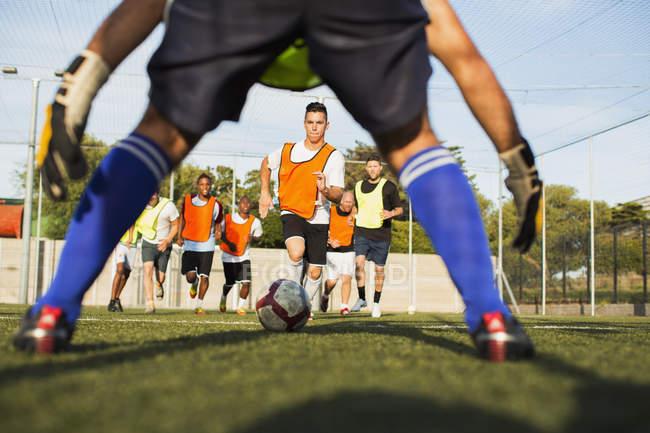 Переглянути через воротаря ніг до футболістів підготовки на полі — стокове фото