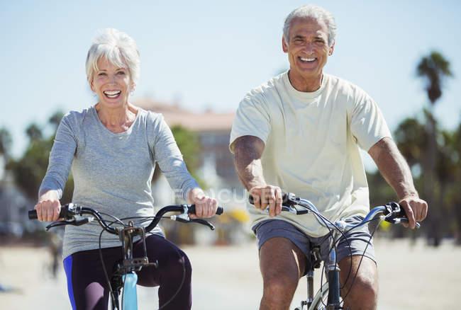 Portrait of senior couple riding bicycles on beach — Stock Photo