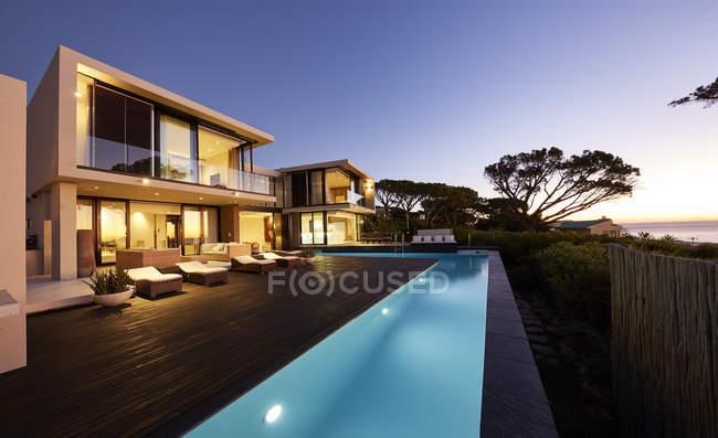 Maison de luxe moderne vitrine terrasse et piscine au coucher du soleil — Photo de stock