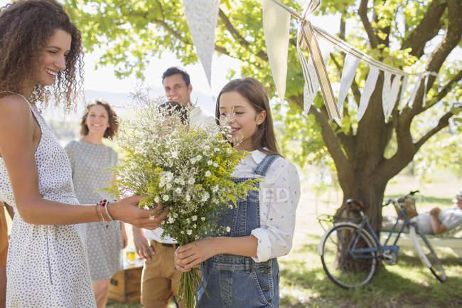 Mujer admirando flores de niña - foto de stock