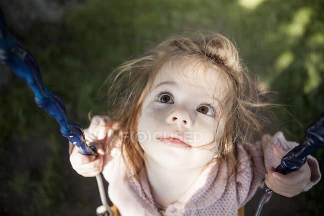Девочка сидит на качелях на улице — стоковое фото