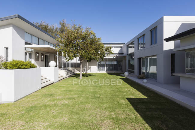 Sunny modern luxury home showcase exterior with courtyard — Stock Photo