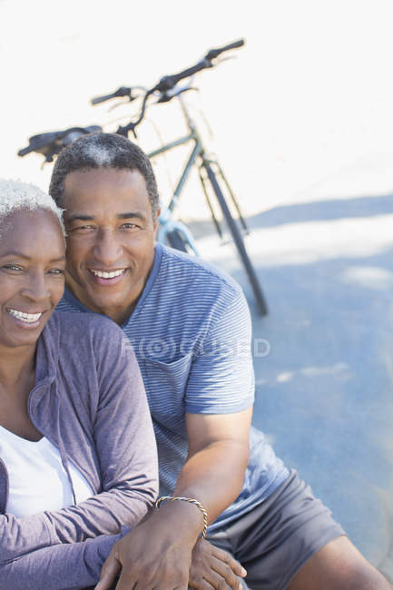 Portrait of smiling senior couple near bicycle — Stock Photo