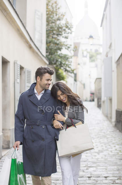 Couple carrying shopping bags on cobblestone street near Sacre Coeur Basilica, Paris, France — Stock Photo