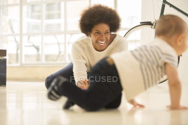 Mutter beobachten Baby Boy Crawl auf Wohnzimmerboden zu Hause — Stockfoto