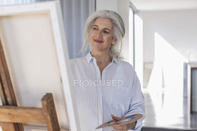 Smiling mature woman with palette painting at canvas on easel — Stock Photo