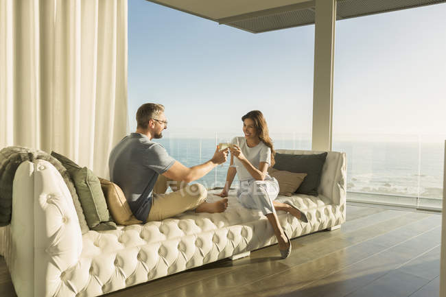 Couple toasting wine glasses on luxury tufted chaise lounge with ocean view — Stock Photo