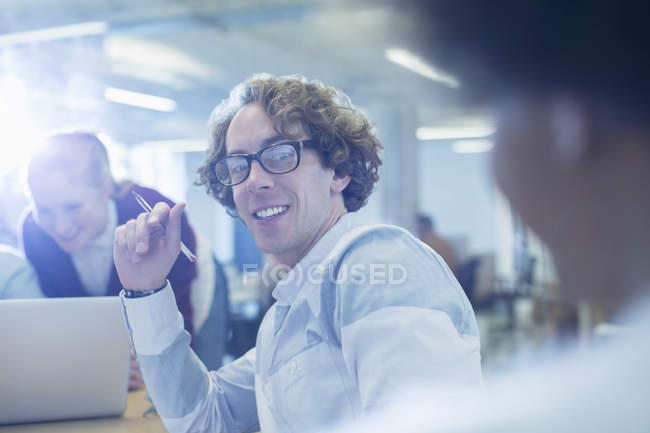 Happy young businessman smiling in office — Stock Photo