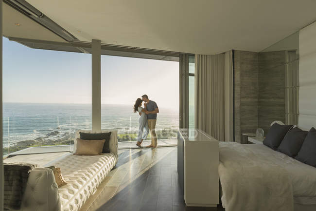 Affectionate couple hugging on modern luxury home showcase bedroom balcony with ocean view — Stock Photo