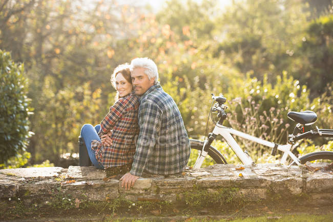Portrait affectionate couple with bicycle resting on stone wall in autumn park — Stock Photo