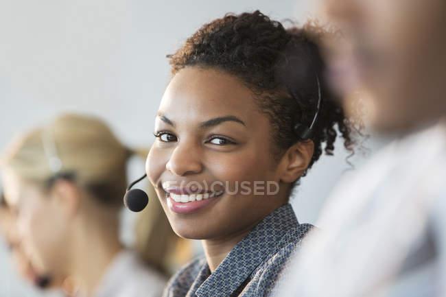 Mulher de negócios usando fone de ouvido no escritório — Fotografia de Stock