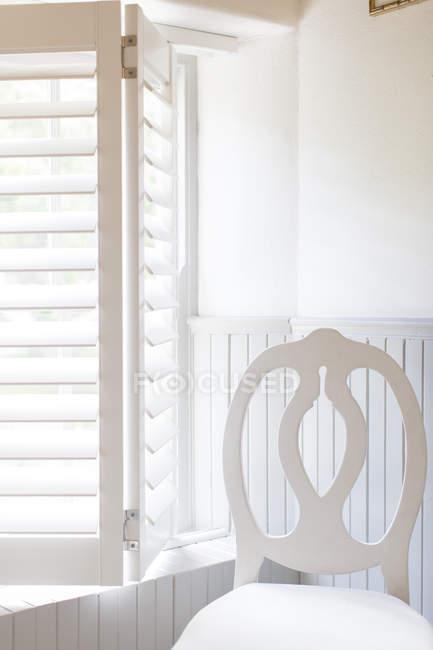 Cadeira por janela com persianas de madeira — Fotografia de Stock