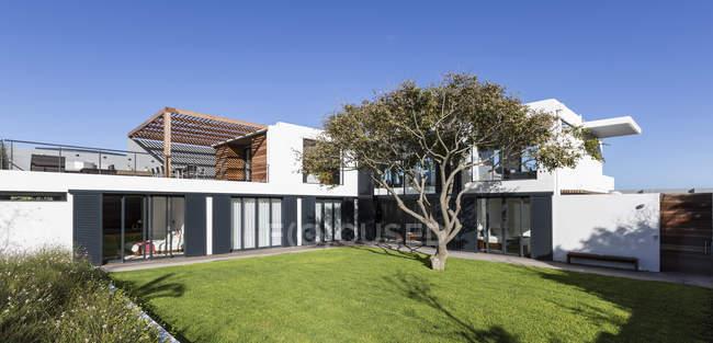Sonnige moderne Luxus home Schaufenster Außenbereich mit Garten und Baum — Stockfoto