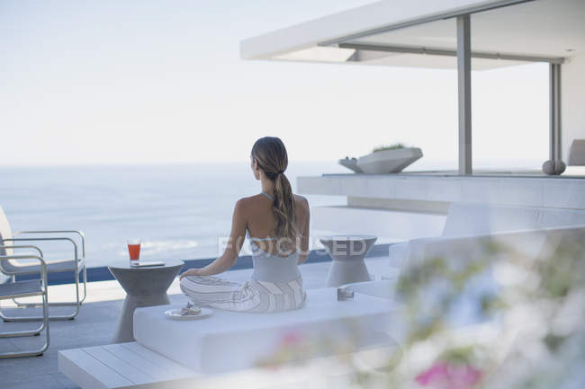 Serene woman meditating on modern, luxury home showcase exterior patio with ocean view — Stock Photo