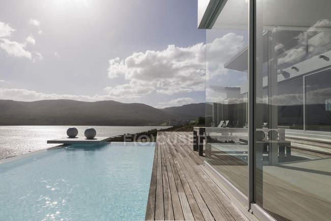 Солнечный, спокойный современный роскошный дом с бассейном и видом на океан — стоковое фото