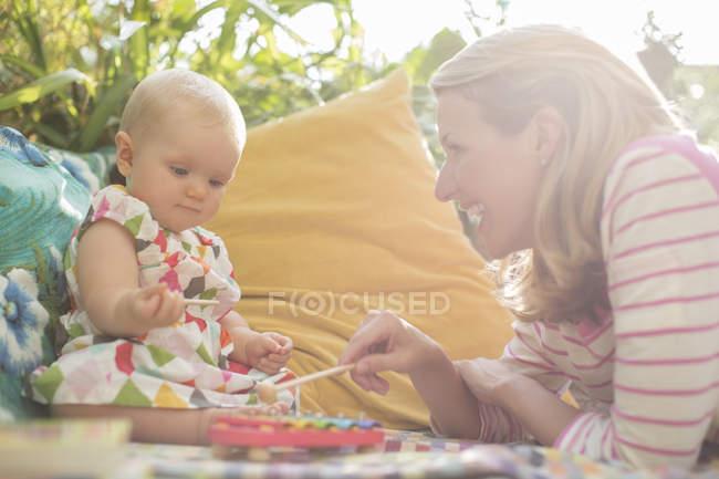 Мать и девочка играют с ксилофоном на открытом воздухе — стоковое фото