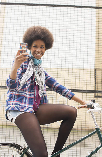 Happy young woman taking self-portrait on bicycle — Stock Photo