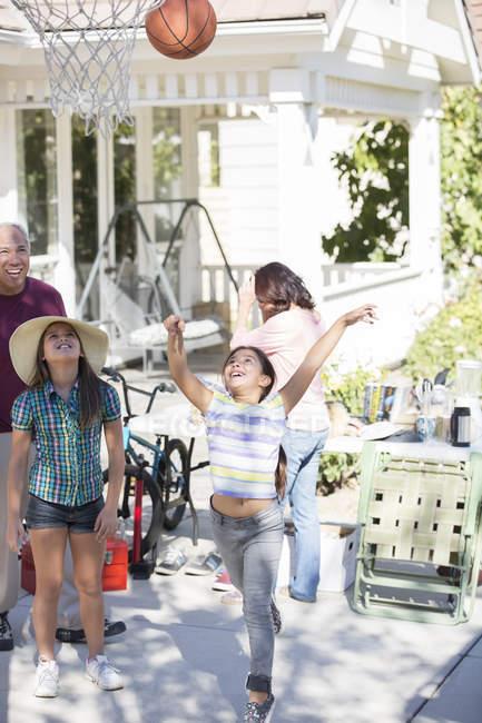 Grandparents watching granddaughters play basketball — Stock Photo