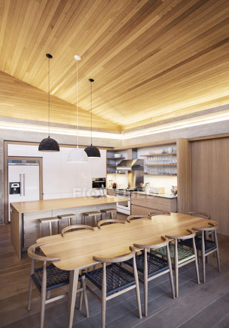 Illuminated slanted wood ceiling over kitchen — Stock Photo