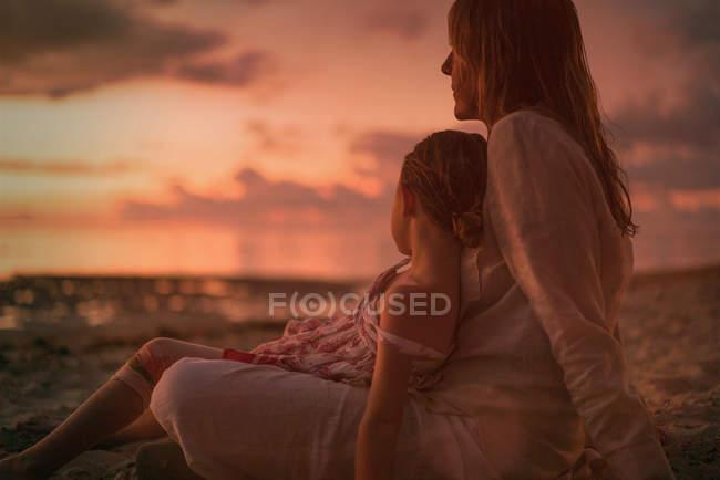 Gelassene Mutter und Tochter entspannen sich in der Abenddämmerung am Strand — Stockfoto