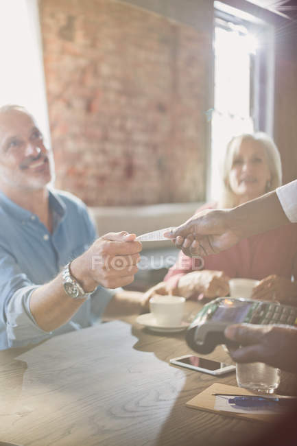 Waiter with credit card reader giving man receipt at restaurant table — Stock Photo