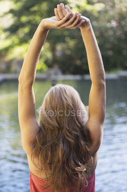 Woman stretching by pool outdoors — Stock Photo