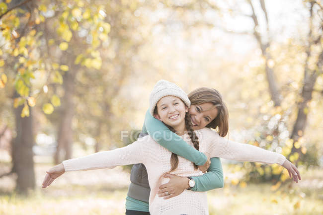 Portrait mother hugging daughter with arms outstretched among autumn leaves — Stock Photo