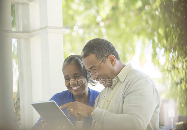 Happy senior couple using digital tablet on porch — Stock Photo