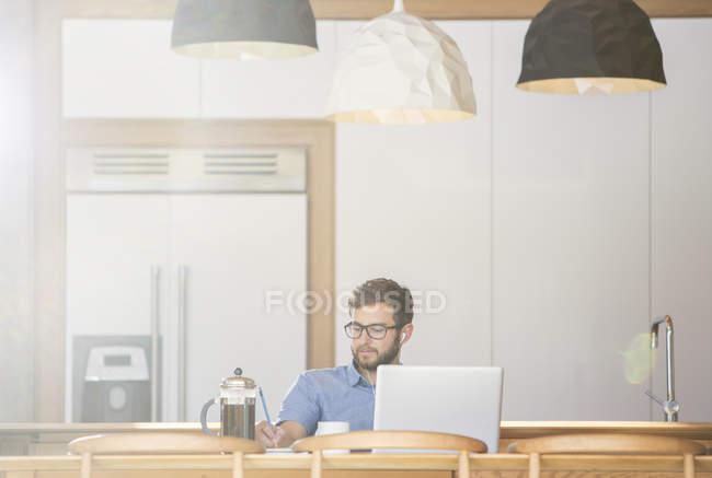 Людина, написавши на ноутбуці в кухні з французької преси кави — стокове фото