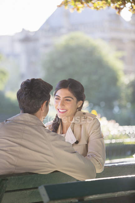 Young couple talking on park bench — Stock Photo