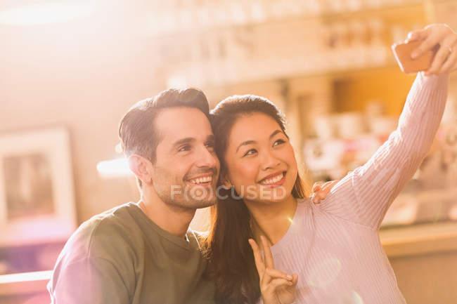 Casal sorridente gesticulando sinal de paz levando selfie com telefone da câmera — Fotografia de Stock
