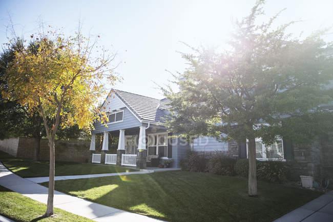 Sol brilhando sobre casa e árvores — Fotografia de Stock