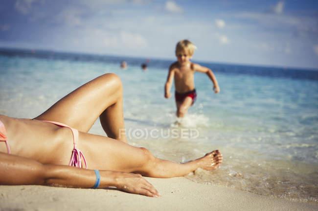 Son running toward mother sunbathing on sunny tropical beach — Stock Photo
