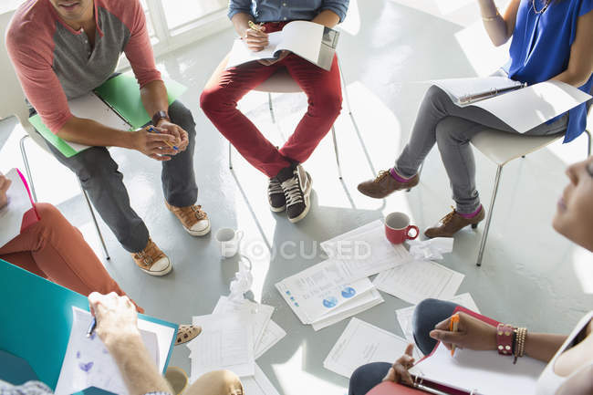 Creative business people meeting with coffee and paperwork in circle of chairs — Stock Photo