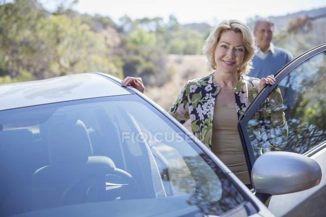 Портрет щасливі старший жінка, спираючись на автомобіль — стокове фото